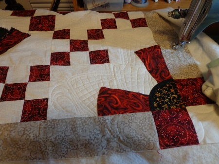 some white on white quilting on the corners in the bows