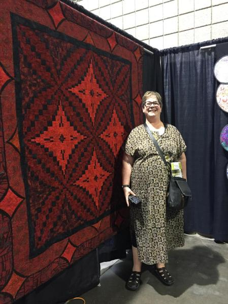kathy in front of royal red kings puzzle quilt